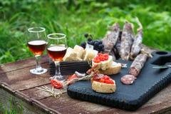 Bruschetta, fette di baguette guarnite con aglio, pomodoro e salsiccia, fine su su un bordo di legno Immagine Stock Libera da Diritti