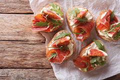 Bruschetta with figs, prosciutto, arugula and cream cheese close Royalty Free Stock Image