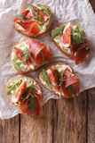 Bruschetta with figs, prosciutto, arugula and cream cheese close Stock Photos