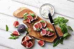 Bruschetta fresco dos figos, da manjericão e do queijo creme na tabela branca Imagens de Stock Royalty Free