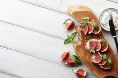 Bruschetta fresco dos figos, da manjericão e do queijo creme na tabela branca Foto de Stock Royalty Free