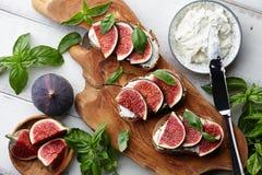 Bruschetta fresco dos figos, da manjericão e do queijo creme na tabela branca Foto de Stock