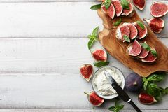 Bruschetta fresco dos figos, da manjericão e do queijo creme na tabela branca Fotografia de Stock