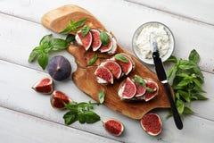 Bruschetta fresco dos figos, da manjericão e do queijo creme na tabela branca Imagem de Stock
