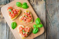 Bruschetta with fresh tomato, garlic and basil salsa. Italian bruschetta with tomato and green basil salsa on wooden background royalty free stock image