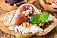 Bruschetta with goat cheese, figs, nuts and honey, selective focus. Italian appetizer close-up. stock image