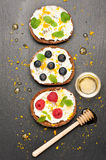 Bruschetta with goat cheese, honey and fresh berries on a stone background. top view Royalty Free Stock Images