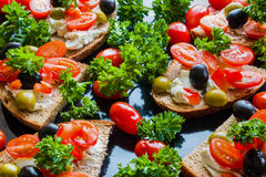 Bruschetta with green and black olives, feta cheese, cherry tomatoes, parsley and red pepper on black background Royalty Free Stock Image
