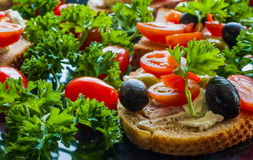 Bruschetta with green and black olives, feta cheese, cherry tomatoes, parsley and red pepper on black background. Healthy snack, breakfast, brunch Royalty Free Stock Photo