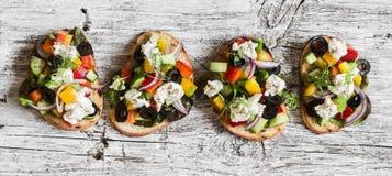 Bruschetta grego em uma placa rústica de madeira, vista superior do estilo da salada Aperitivos deliciosos fotos de stock