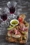 Bruschetta with  ham, olives, cherry tomatoes in olive Board and red wine Royalty Free Stock Photography