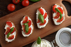 Bruschetta hecho en casa con queso, el tomate y la albahaca en tabla de cortar Foto de archivo