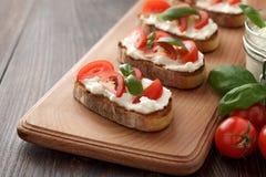 Bruschetta hecho en casa con queso Feta, albahaca y tomates en tabla de cortar Foto de archivo libre de regalías