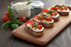 Bruschetta hecho en casa con queso Feta, los tomates y la albahaca del queso en tabla de cortar en la tabla de madera Foto de archivo