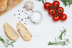 Bruschetta ingredients with mozzarella, cherry tomatoes and fresh garden rosemary. Top view with space for your text stock photos