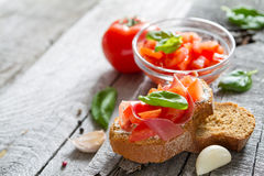 Bruschetta and ingredients on rustic wood background Stock Photography
