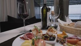 Bruschetta, italian toasted bread with prosciutto, olives, tomato and cheese top viewv in moder restaurant stock video footage