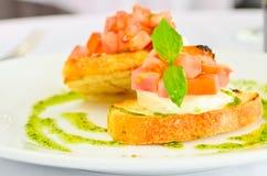 Bruschetta italiana con i pomodori del formaggio e un condimento del basilico Fotografie Stock