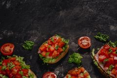 Bruschetta italiana con i pomodori, la salsa della mozzarella e le foglie tagliati dell'insalata Aperitivo o spuntino italiano tr immagine stock