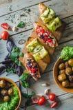 Bruschetta italiana con lo zucchini, i pomodori arrostiti, il formaggio di capra e le erbe su un bordo di legno fotografia stock libera da diritti