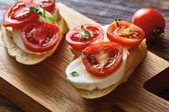 Bruschetta italiana del pomodoro con le verdure tagliate, la mozzarella, le erbe ed il pane crostoso di ciabatta su un bordo di l fotografia stock