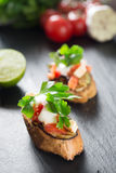 Bruschetta italiana del pomodoro saporito saporito, sulle fette di baguette tostate guarnite con prezzemolo Fotografia Stock