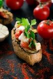 Bruschetta italiana del pomodoro saporito saporito, sulle fette di baguette tostate guarnite con prezzemolo e melanzana Fotografie Stock Libere da Diritti