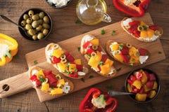 Bruschetta italiano com azeitonas roasted do queijo de cabra das pimentas imagem de stock royalty free