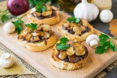 Bruschetta italiano com cogumelos e as cebolas vermelhas caramelizadas em um fundo de madeira Foco seletivo imagens de stock