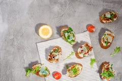 Bruschetta italiano com salmões, tomates, queijo e pesto da manjericão em um fundo concreto ou de pedra cinzento foto de stock royalty free