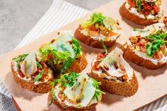 Bruschetta italiano con los salmones, los tomates, el queso y el pesto de la albahaca en un fondo concreto o de piedra gris Fotos de archivo