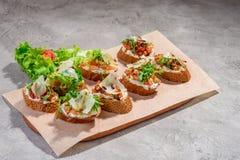 Bruschetta italiano con los salmones, los tomates, el queso y el pesto de la albahaca en un fondo concreto o de piedra gris Imagen de archivo