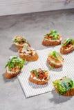 Bruschetta italiano con los salmones, los tomates, el queso y el pesto de la albahaca en un fondo concreto o de piedra gris Imagen de archivo libre de regalías