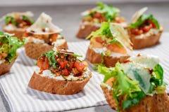 Bruschetta italiano con los salmones, los tomates, el queso y el pesto de la albahaca en un fondo concreto o de piedra gris Fotografía de archivo libre de regalías