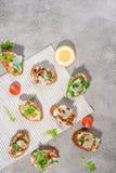 Bruschetta italiano con los salmones, los tomates, el queso y el pesto de la albahaca en un fondo concreto o de piedra gris Foto de archivo libre de regalías