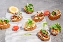 Bruschetta italiano con los salmones, los tomates, el queso y el pesto de la albahaca en un fondo concreto o de piedra gris Fotografía de archivo