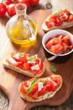 Bruschetta italiano con los tomates, el parmesano, el ajo y el aceite de oliva Imagenes de archivo