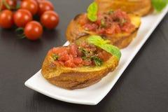 Bruschetta italiano con los tomates y la albahaca Imágenes de archivo libres de regalías