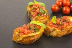 Bruschetta italiano con los tomates y la albahaca Foto de archivo libre de regalías