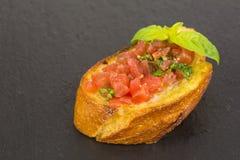 Bruschetta italiano con los tomates y la albahaca Fotos de archivo libres de regalías