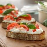 Bruschetta italiano con queso, el tomate y la albahaca en tabla de cortar Imagen de archivo