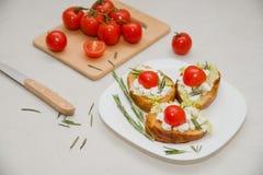 Bruschetta italiano con queso suave, los tomates, el romero y la ensalada fresca en la placa Espacio para el texto Fotos de archivo libres de regalías