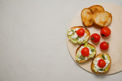 Bruschetta italiano con queso suave, los tomates, el romero y la ensalada fresca en la placa Espacio para el texto Foto de archivo libre de regalías