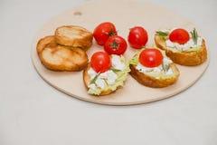 Bruschetta italiano con queso suave, los tomates, el romero y la ensalada fresca en la placa Espacio para el texto Fotos de archivo