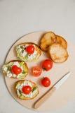 Bruschetta italiano con queso suave, los tomates, el romero y la ensalada fresca en la placa Espacio para el texto Imagen de archivo