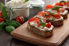 Bruschetta italiano del aperitivo con ciabatta, queso Feta, los tomates y la albahaca en tabla de cortar Fotos de archivo