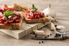 Bruschetta italiano del tomate en fondo de madera rústico imagen de archivo