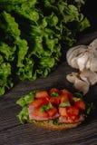 Bruschetta italiano delicioso de los antipasti con las hojas tajadas del tomate, de la coronilla de la carne, de la salsa, del qu fotografía de archivo
