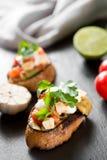 Bruschetta italiano do tomate saboroso saboroso, em fatias de baguette brindado decorado com salsa Fotos de Stock Royalty Free