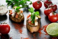 Bruschetta italiano do tomate saboroso saboroso, em fatias de baguette brindado decorado com salsa Fotografia de Stock Royalty Free